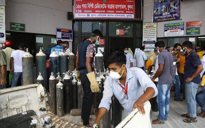 In this picture taken on July 2, 2021 Men unload medical oxygen cylinders at the entrance of a government hospital dedicated to treat Covid-19 coronavirus patients in Khulna. - AFP