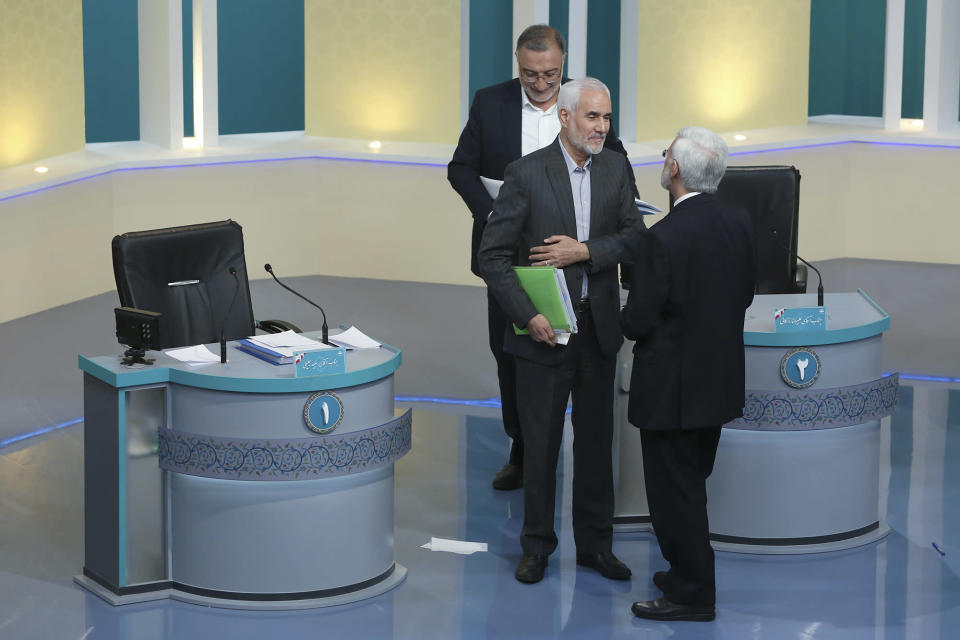 """In this picture made available by Young Journalists Club, YJC, presidential candidates for June 18, elections Mohsen Mehralizadeh, center, Alireza Zakani, top, and Saeed Jalili, talk at the conclusion of a part of the final debate of the candidates at a state-run TV studio in Tehran, Iran, Saturday, June 12, 2021. Iran's seven presidential candidates offered starkly different views Saturday in the country's final debate, with hard-liners describing those seeking ties with the West as """"infiltrators"""" and the race's sole moderate warning a hard-line government would only bring more sanctions for the Islamic Republic. (Morteza Fakhri Nezhad/ Young Journalists Club, YJC via AP)"""