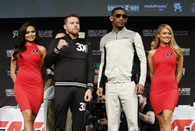 Canelo Alvarez, center left, and Daniel Jacobs, center right, pose for photographers at a news conference for their middleweight title boxing match Wednesday, May 1, 2019, in Las Vegas. The two are scheduled to fight Saturday in Las Vegas. (AP Photo/John Locher)