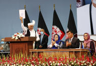 Afghan President Ashraf Ghani holds up the resolution on the last day of an Afghan Loya Jirga or traditional council, in Kabul, Afghanistan, Sunday, Aug. 9, 2020. The council concluded Sunday with hundreds of delegates agreeing to free 400 Taliban members, paving the way for an early start to negotiations between Afghanistan's warring sides. (AP Photo)