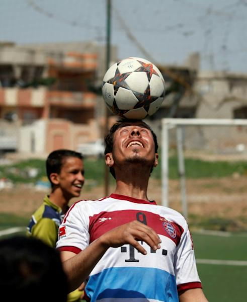 An Iraqi player, sporting the jersey of German club Bayern Munich, shows his skills ahead of a football match in eastern Mosul's al-Salam neighbourhood