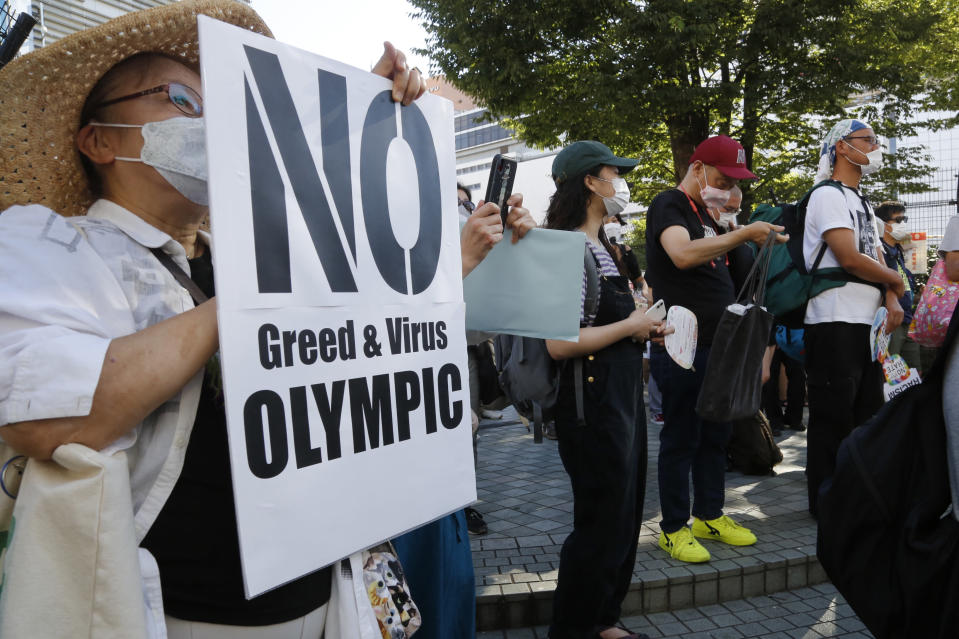 People gather for a rally in Tokyo's Shinjuku shopping district Sunday, July 18, 2021, to protest against the Olympics starting from July 23. They held signs that said No Olympics.(AP Photo/Yuri Kageyama)