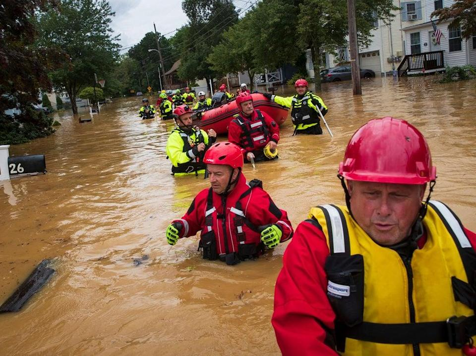 Members of the New Market Volunteer Fire Company perform a secondary search during an evacuation effort following a flash flood, as Tropical Storm Henri makes landfall, in Helmetta, New Jersey (AFP via Getty Images)