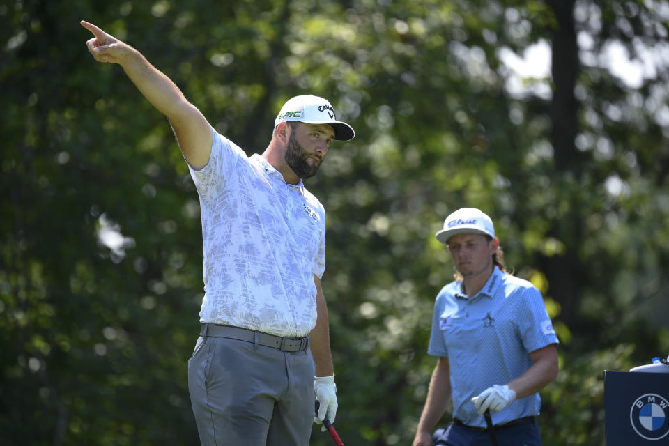 Jon Rahm, of Spain, left, gestures as his tee shot from the fifth hole goes left as Cameron Smith, of Australia, right, approaches the tee box during the first round of the BMW Championship golf tournament, Thursday, Aug. 26, 2021, at Caves Valley Golf Club in Owings Mills, Md. (AP Photo/Nick Wass)