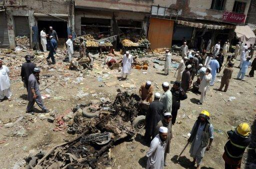 Pakistani security officials inspect the site of a bomb explosion in the main bazaar of Landi Kotal