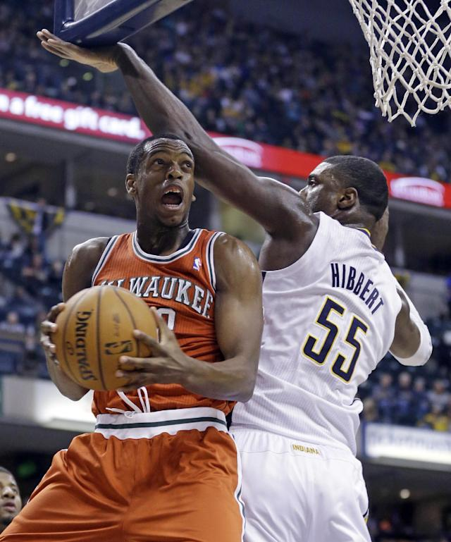 Milwaukee Bucks forward Khris Middleton, left, looks to shoot against Indiana Pacers center Roy Hibbert during the first half of an NBA basketball game in Indianapolis, Friday, Nov. 15, 2013. (AP Photo/Michael Conroy)