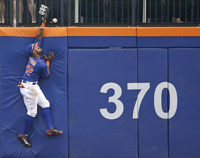 New York Mets left fielder Eric Young Jr. leaps in vain at the wall trying to catch a solo home run hit by Washington Nationals' Adam LaRoche in the second inning of a baseball game, Thursday, Sept. 12, 2013, in New York. The umpires reviewed the play using video replay and ruled it a home run. (AP Photo/Kathy Willens)