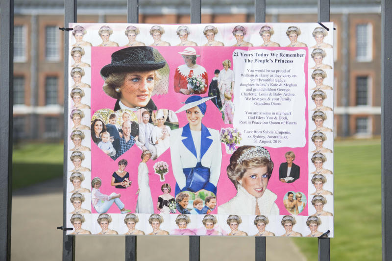 A pink poster with images and memories of Princess Diana sits on the gates of Kensington Palace on August 31 2019