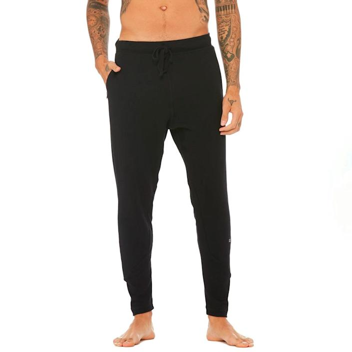 """Leave it to Alo to come through with an extremely comfy pair of sweatpants that'll finally get him to toss those ancient flannel bottoms. $98, Alo Yoga. <a href=""""https://www.aloyoga.com/products/m5079r-the-triumph-sweatpant-solid-black-triblend"""" rel=""""nofollow noopener"""" target=""""_blank"""" data-ylk=""""slk:Get it now!"""" class=""""link rapid-noclick-resp"""">Get it now!</a>"""