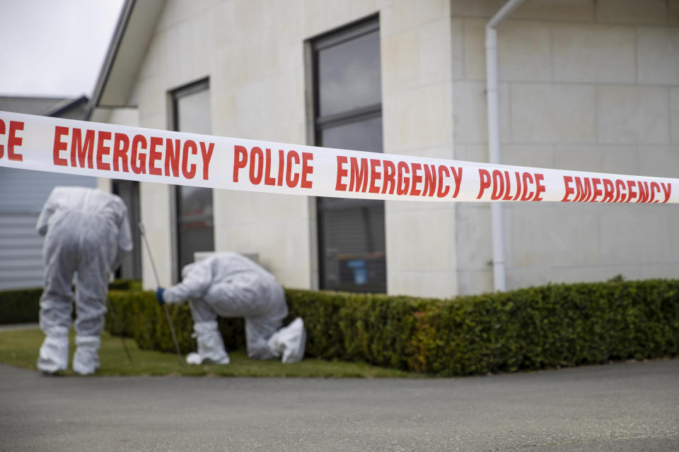 Police search a garden near a house where three children were found dead in the South Island town of Timaru, New Zealand, Friday, Sept. 17, 2021. Three young children who had just moved to New Zealand from South Africa have died in what police are investigating as homicide. (George Heard/New Zealand Herald via AP)