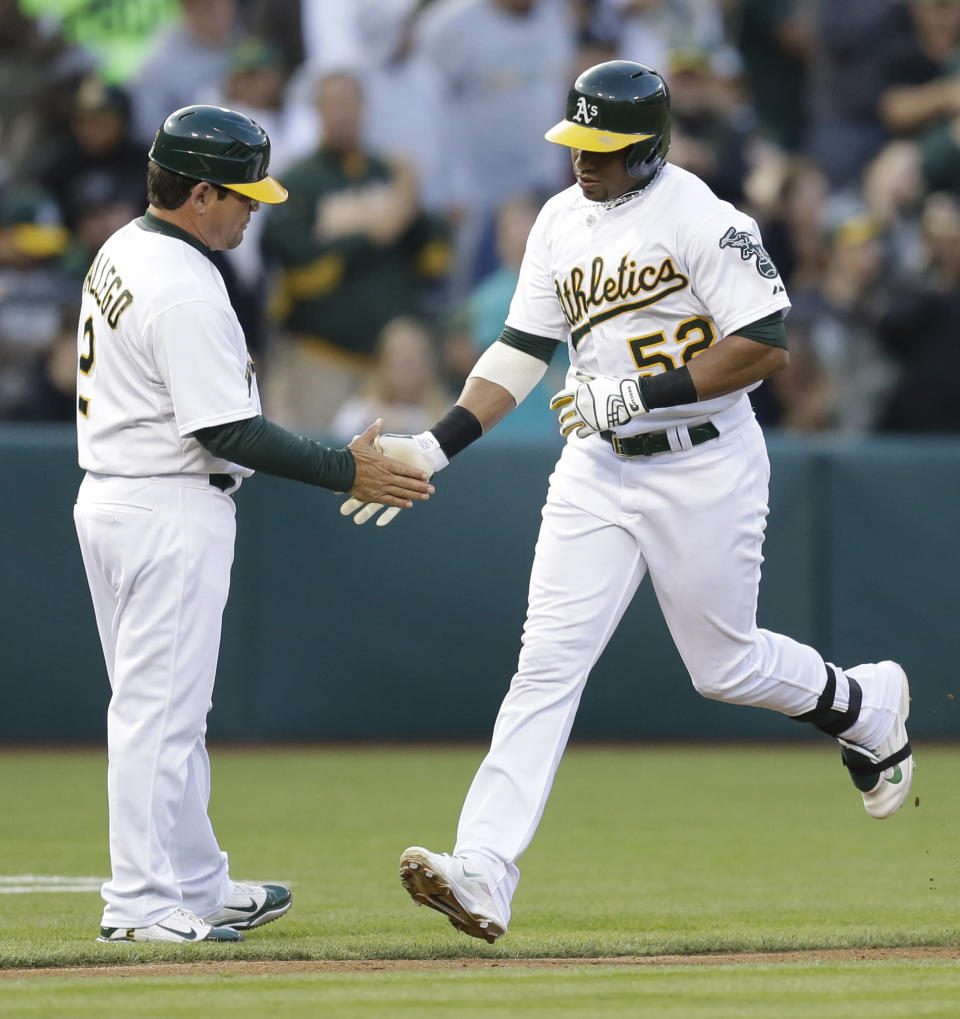 Oakland Athletics' Yoenis Cespedes, right, is congratulated by third base coach Mike Gallego after hitting a home run off Boston Red Sox pitcher Jake Peavy in the third inning of a baseball game Thursday, June 19, 2014, in Oakland, Calif. (AP Photo/Ben Margot)