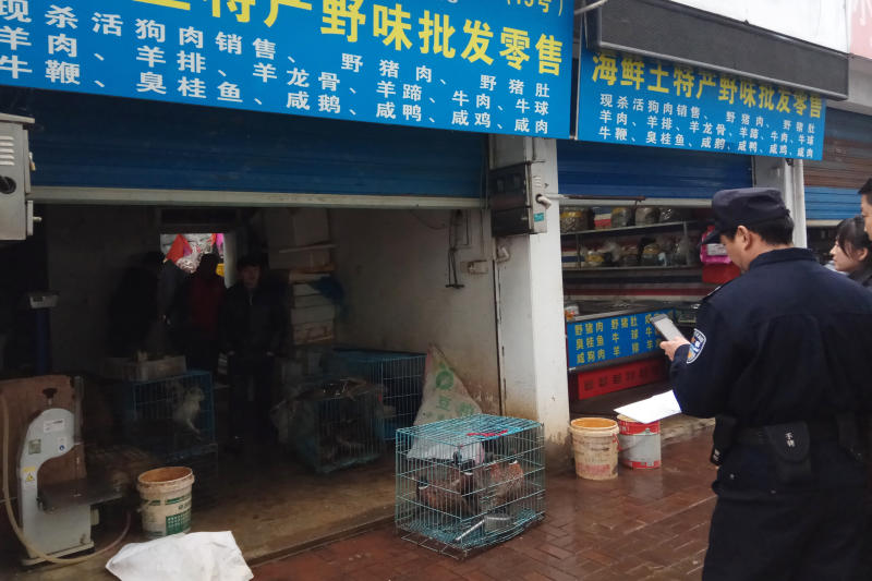 FILE - In this Jan. 9, 2020, file photo provided by the Anti-Poaching Special Squad, police gather outside a store suspected of trafficking in wildlife in the city of Guangde in central China's Anhui province. As China enforces a temporary ban on the wildlife trade to contain the outbreak of a new virus, many are calling for a more permanent solution before disaster strikes again. (Anti-Poaching Special Squad via AP, File)