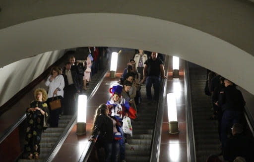 In this June 14, 2018 photo a woman in Russian colors stands on an escalator of the Metro after Russia won the opening match between Russia and Saudi Arabia during the 2018 soccer World Cup in Moscow, Russia. (AP Photo/Rebecca Blackwell)