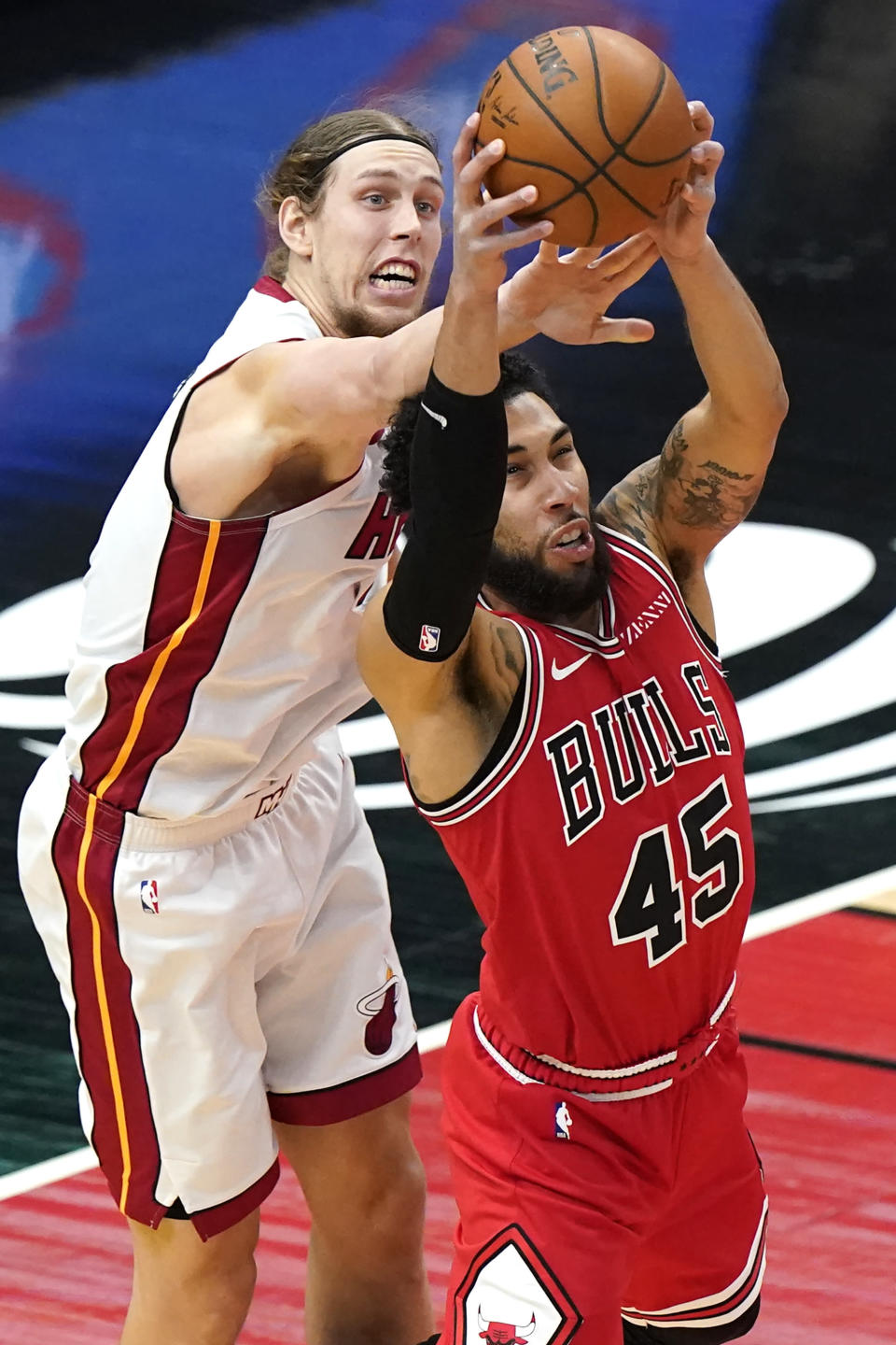 Chicago Bulls guard Denzel Valentine, right, rebounds the ball against Miami Heat forward Kelly Olynyk during the first half of an NBA basketball game in Chicago, Friday, March 12, 2021. (AP Photo/Nam Y. Huh)
