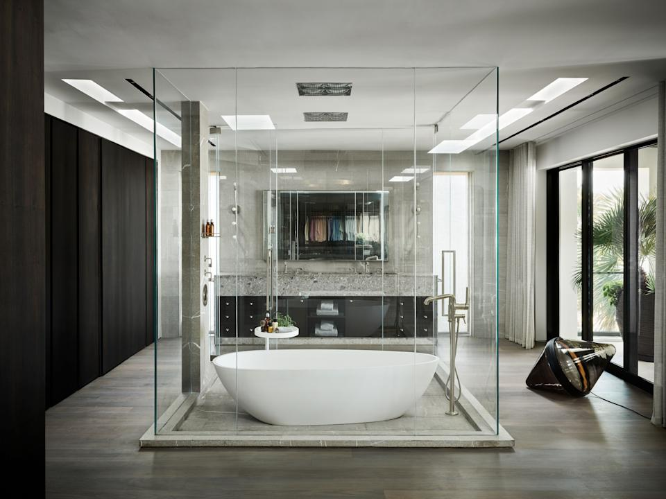 """<div class=""""caption""""> Joyner wanted his master bathroom to be able to take full advantage of its unparalleled ocean views. The <a href=""""https://www.rifra.com/en/index.aspx"""" rel=""""nofollow noopener"""" target=""""_blank"""" data-ylk=""""slk:RiFRA"""" class=""""link rapid-noclick-resp"""">RiFRA</a> tub sits in the middle of the room, and two separate <a href=""""https://www.waterworks.com/us_en/"""" rel=""""nofollow noopener"""" target=""""_blank"""" data-ylk=""""slk:Waterworks"""" class=""""link rapid-noclick-resp"""">Waterworks</a> shower heads are installed in the ceiling: one for taking a shower in the bathtub and one that is separate. A nearby floor lamp by <a href=""""https://www.danyeffet.com/"""" rel=""""nofollow noopener"""" target=""""_blank"""" data-ylk=""""slk:Dan Yeffet"""" class=""""link rapid-noclick-resp"""">Dan Yeffet</a> is the perfect accompaniment for nighttime soaks. Part of Joyner's large closet can be seen in the reflection of the mirror over the sinks. </div>"""