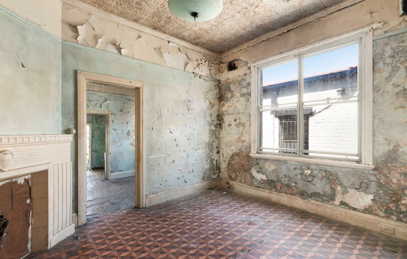 Pictured is the living room of the property with peeling paint on the walls.