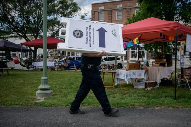 An EMT worker carries a sign advertising free vaccinations against Covid-19 at a farmers market in Northfield, Vermont on June 28, 2021