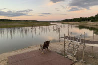 An empty rocking chair overlooks tree stumps, once submerged in Wixom Lake, at sunset July 30, 2020, near Edenville, Michg. Nature is returning to the dry beds of a string of mid-Michigan lakes that drained in May after two dams failed during torrential rains. (AP Photo/ Jeff McMillan)
