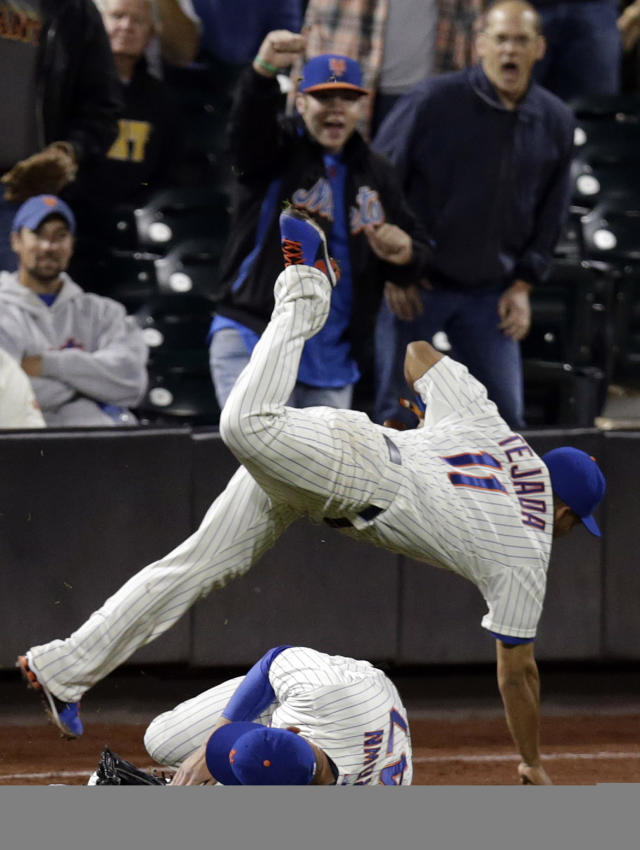 New York Mets shortstop Ruben Tejada (11) trips over left fielder Andrew Brown after catching San Francisco Giants' Angel Pagan's ninth-inning fly-out in left field during a baseball game on Wednesday, Sept. 18, 2013, in New York. (AP Photo/Kathy Willens)