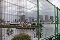 <p>TOKYO, JAPAN - AUGUST 02: The Olympic Rings are seen through a security fence surrounding Odaiba Marine Park Olympic venue on August 2, 2021 in Tokyo, Japan. Despite a recent surge in Covid-19 cases in Tokyo, Japanese Prime Minister Yoshihide Suga stated on Friday that adequate measures are in place to prevent coronavirus infections spreading from Olympic athletes and staff to the wider population. Mr. Suga also announced that Tokyo's neighboring prefectures of Chiba, Kanagawa, Saitama will be added to the state of emergency that currently covers the capital and which runs through to August 31st. (Photo by Carl Court/Getty Images)</p>