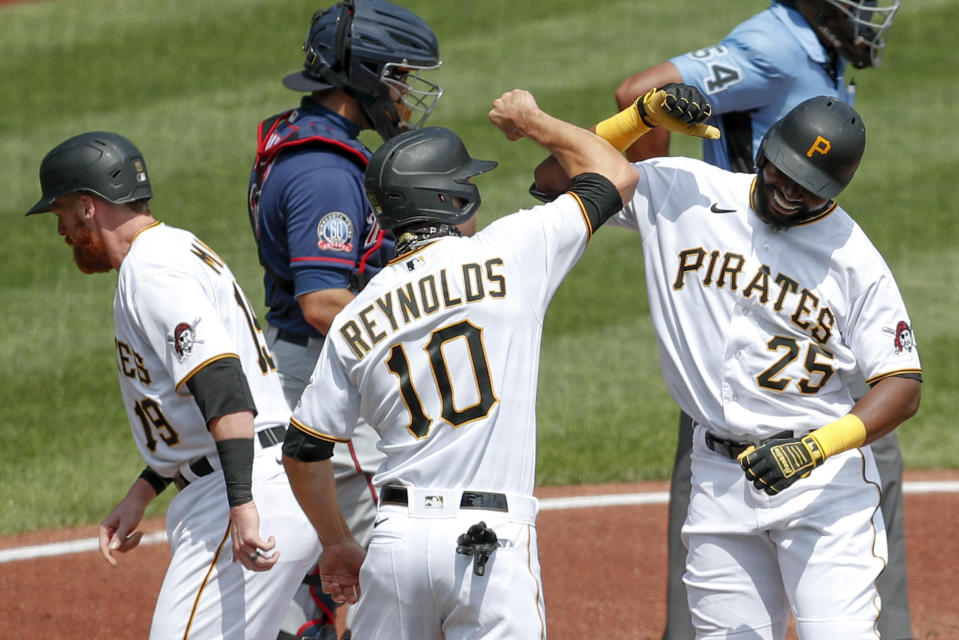 Pittsburgh Pirates' Gregory Polanco (25) celebrates with Bryan Reynolds (10) and Colin Moran (19) after Polanco hit a home run scoring them in the second inning of a baseball game against the Minnesota Twins, Thursday, Aug. 6, 2020, in Pittsburgh. Minnesota Twins catcher Alex Avila, is at top center. (AP Photo/Keith Srakocic)