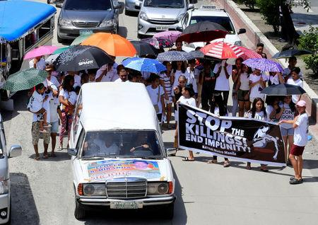Relatives and loved ones of Leover Miranda, 39, a drug-related killings victim, hold a streamer calling to stop the continuing rise of killings due to the President Rodrigo Duterte's ruthless war on drugs, during a funeral march at the north cemetery in metro Manila, Philippines August 20, 2017. REUTERS/Romeo Ranoco