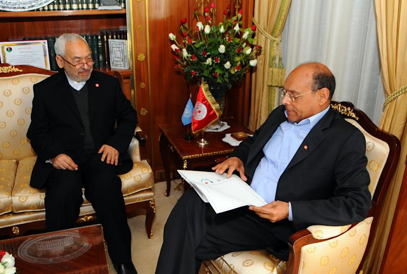 President Moncef Marzouki, right, listens to Ennahda ruling party's leader Rached Ghannouchi prior to a meeting at the presidential palace in Carthage near Tunis, Friday, Feb. 22, 2013. Tunisian President Moncef Marzouki on Friday has asked incumbent Interior Minister Ali Laarayedh from the ruling Ennahdha to form a new government in two weeks, according to the presidential office. (AP Photo/Hassene Dridi)