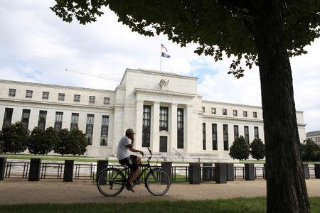 FILE PHOTO: FILE PHOTO: A cyclist passes the Federal Reserve building in Washington, DC