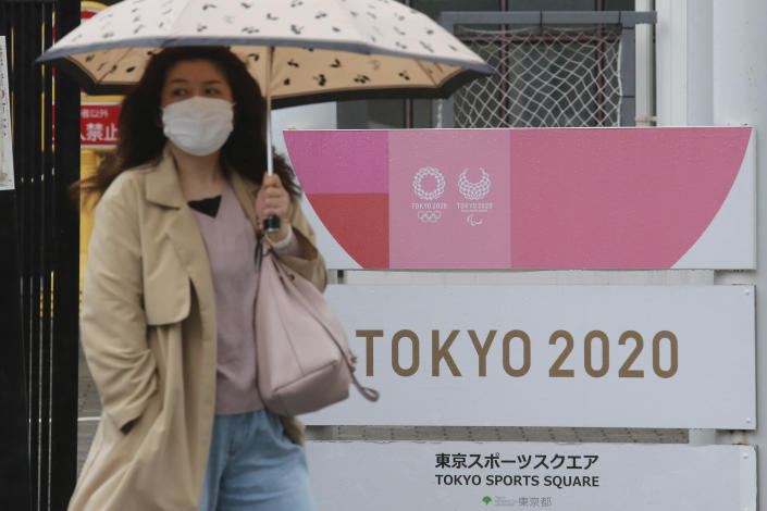 A woman walks by signage to promote the Olympic Games in Tokyo, Monday, April 5, 2021. (AP Photo/Koji Sasahara)