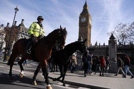 Two mounted police officers ride past the Houses of Parliament, following the attack in Westminster earlier in the week, in London