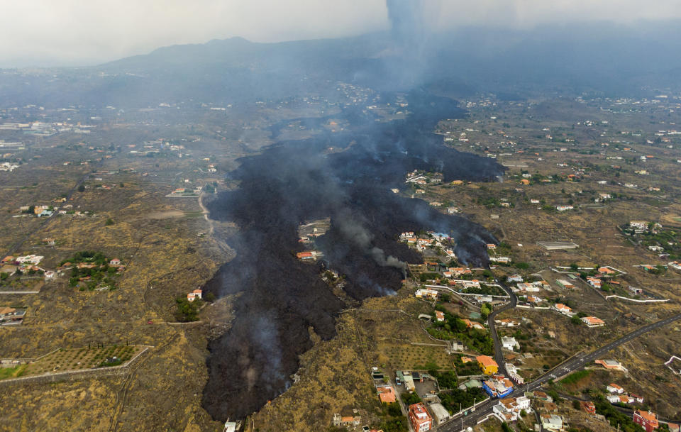 FILE - In this Tuesday, Sept. 21, 2021 file photo, lava from a volcano eruption flows destroying houses on the island of La Palma in the Canaries, Spain. A long-dormant volcano on a small Spanish island in the Atlantic Ocean erupted on Sunday Sept. 19, 2021, forcing the evacuation of thousands of people. Huge plumes of black-and-white smoke shot out from a volcanic ridge where scientists had been monitoring the accumulation of molten lava below the surface. (AP Photo/Emilio Morenatti, File)