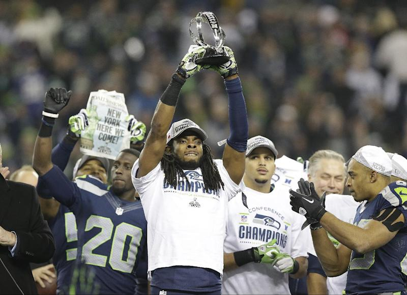 Seattle Seahawks' Richard Sherman holds up the George Halas Trophy after the NFL football NFC Championship game against the San Francisco 49ers Sunday, Jan. 19, 2014, in Seattle. The Seahawks won 23-17 to advance to Super Bowl XLVIII. (AP Photo/Elaine Thompson)