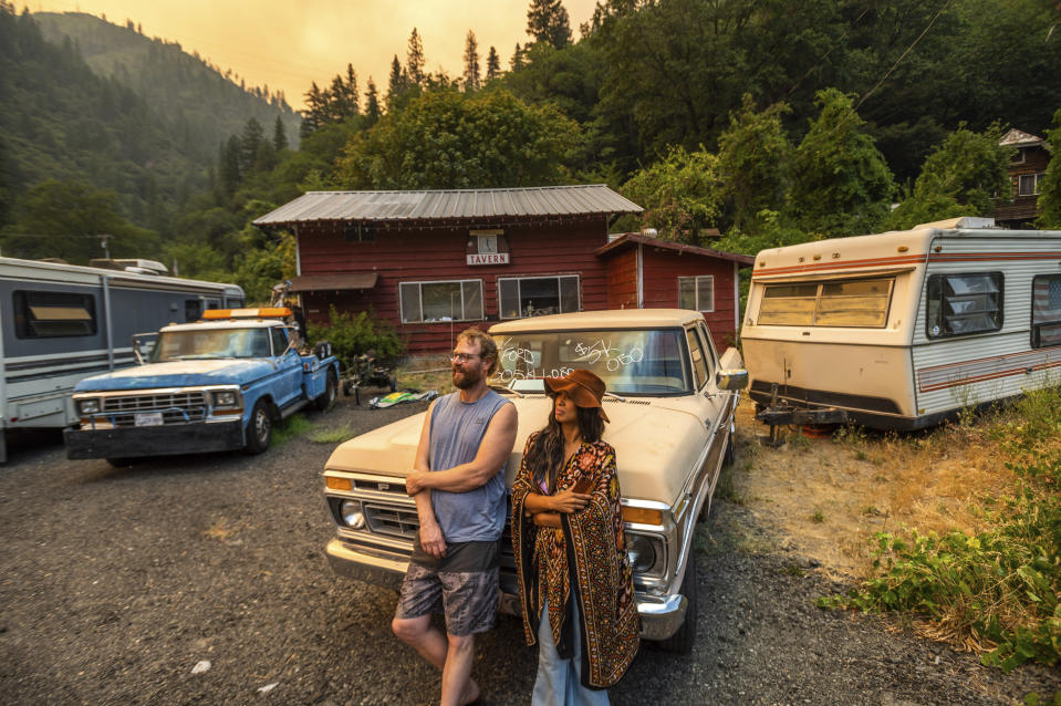 Jessica and Benjamin Bell watch as the Dixie Fire burns along Highway 70 in Plumas National Forest, Calif., on Friday, July 16, 2021. (AP Photo/Noah Berger)