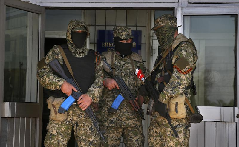 Pro Russian masked armed men guard at the city hall in Kostyantynivka, 35 kilometers (22 miles) south of Slovyansk, eastern Ukraine, Monday, April 28, 2014, after masked militants with automatic weapons seized the hall building. Ukraine's acting government and the West have accused Russia of orchestrating the unrest, which they fear Moscow could use as a pretext for an invasion. (AP Photo/Sergei Grits)