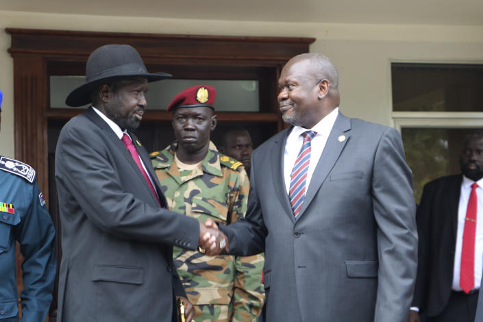 South Sudan's President Salva Kiir left, and opposition leader Riek Machar, right, shake hands after meetings Sunday Oct. 20, 2019, to discuss outstanding issues to the peace deal. Machar made an impassioned plea to a visiting United Nations Security Council delegation that met with him and President Salva Kiir, to urge speedier progress in pulling the country out of a five-year civil war. (AP Photo/Sam Mednick)