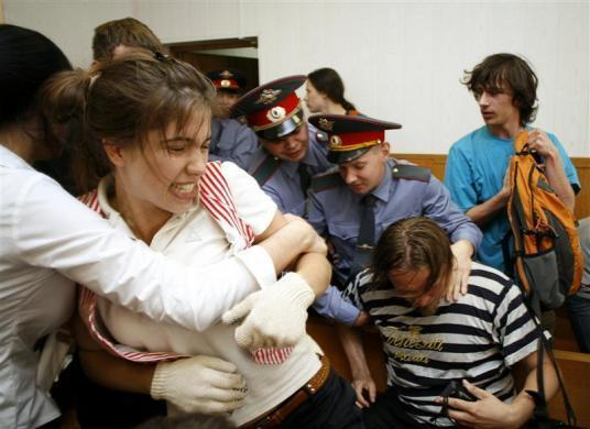 Police remove Nadezhda Tolokonnikova (L) Oleg Vorotnikov (bottom R) and other political activists of the art group Voina from a courtroom after they disrupted a hearing against the director of the Sakharov Centre, in Moscow, May 29, 2009. Accusing the court of political bias, the Voina activists interrupted the procedure with punk rock music played on instruments they smuggled into the court room. Tolokonnikova later became a member of Pussy Riot.