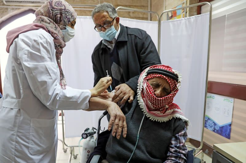A Palestinian man is helped by his son as he receives a vaccination against the coronavirus disease (COVID-19) as Israel continues its national vaccination drive, in East Jerusalem