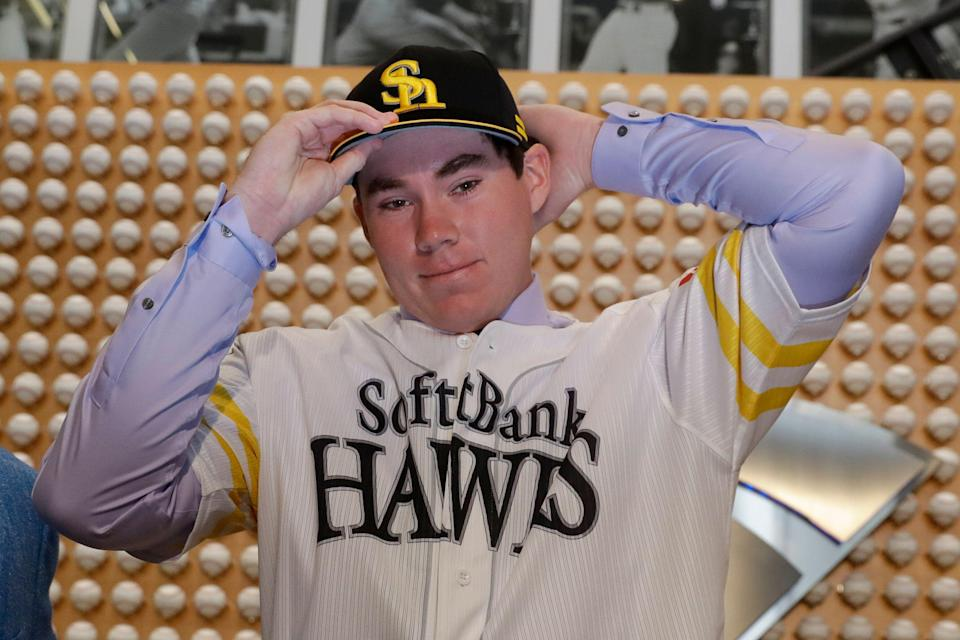 SoftBank Hawks pitcher Carter Stewart Jr. puts on the team's hat during a baseball news conference in Newport Beach, Calif., Thursday, May 30, 2019. After failing to sign with Atlanta and losing a grievance against the Braves, 19-year-old right-hander Carter Stewart has agreed to a six-year contract with the Fukuoka SoftBank Hawks of Japan's Pacific League. (AP Photo/Chris Carlson)