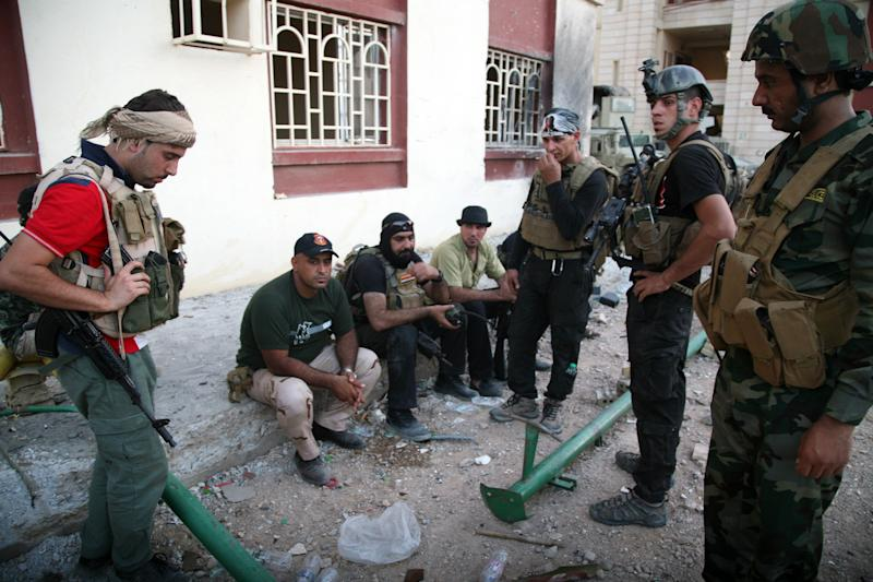Iraqi security forces rest on a sidewalk following clashes with jihadists on September 19, 2014, in Ramadi (AFP Photo/Azhar Shallal)