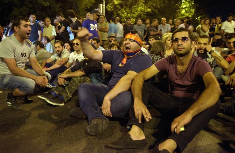 Protestors block a street leading to Erebuni police station seized by gunmen, supporters of fringe jailed opposition leader Zhirair Sefilyan, in Yerevan, Armenia, early on July 31, 2016