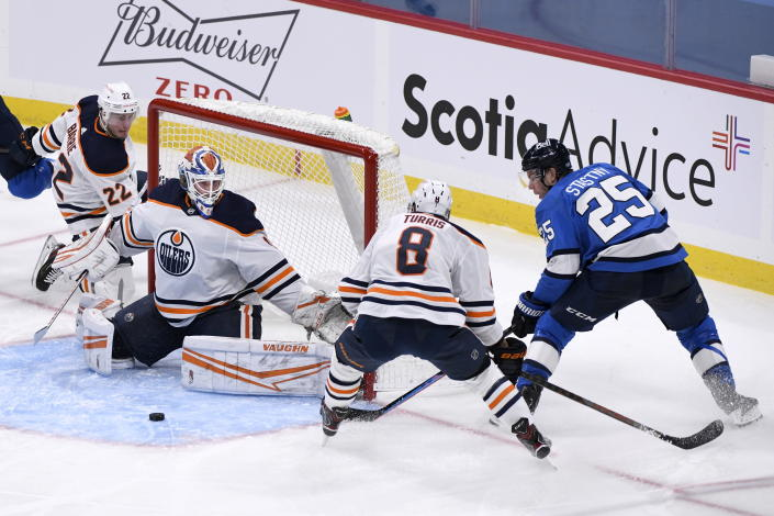 Edmonton Oilers goaltender Mikko Koskinen (19) makes a save on Winnipeg Jets' Paul Stastny (25) as Oilers' Kyle Turris (8) defends during the second period of an NHL hockey game, Sunday, Jan. 24, 2021 in Winnipeg, Manitoba. (Fred Greenslade/The Canadian Press via AP)