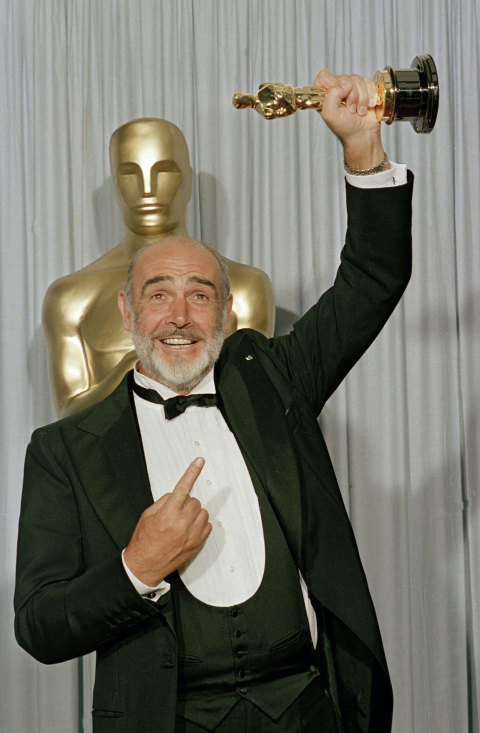 "FILE - In this file photo dated April 11, 1988, Sean Connery holds up his best supporting actor Oscar for ""The Untouchables"" at the 60th annual Academy Awards in Los Angeles, Ca., USA. Scottish actor Sean Connery, considered by many to have been the best James Bond, has died aged 90, according to an announcement from his family. (AP Photo/Lennox McLendon, FILE)"