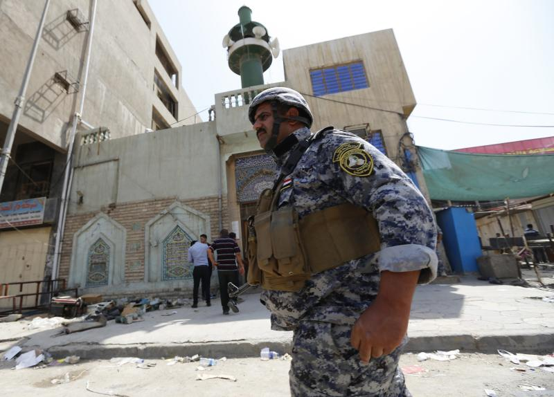 A member of the Iraqi security forces stands guard outside a Shi'ite mosque after a bomb attack in Baghdad