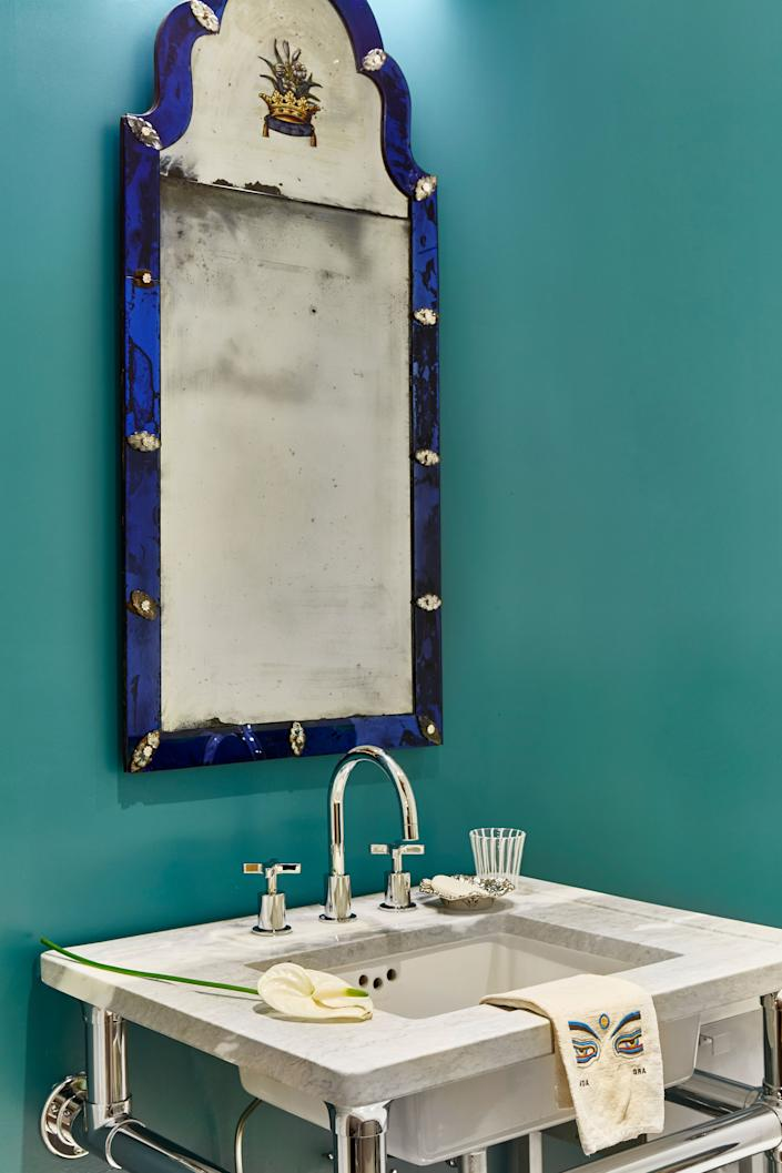 "<div class=""caption""> Khandwala likes to reserve the bold hues for the bathrooms. For this one, he chose <a href=""https://www.farrow-ball.com/en-us"" rel=""nofollow noopener"" target=""_blank"" data-ylk=""slk:Farrow & Ball"" class=""link rapid-noclick-resp"">Farrow & Ball</a>'s Arsenic, which contrasts with the mirror's blue-glass frame. The towels come from Nancy Stanley Waud Fine Linens. </div>"