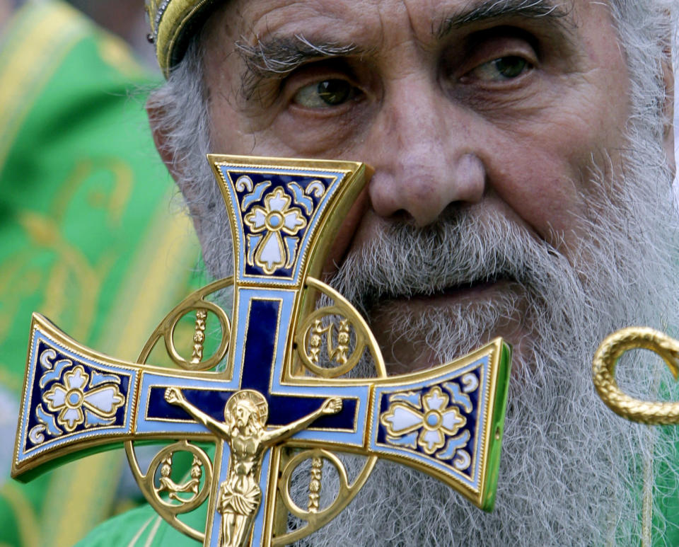 FILE - In this May 24, 2012, file photo, Serbian Orthodox Church Patriarch Irinej holds a cross during a procession marking Belgrade's patrons saint day, Spasovdan, in downtown Belgrade. Serbia's Orthodox Church said Friday, Nov. 20, 2020, the leader, Patriarch Irinej, has died after testing positive for the coronavirus. He was 90. (AP Photo/Darko Vojinovic, File)