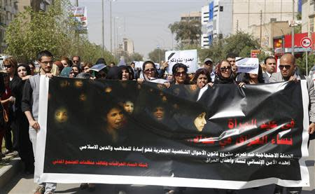 """Iraqi Protesters hold banner during a demonstration against the draft of the """"Al-Jafaari"""" Personal Status Law during International Women's Day in Baghdad"""