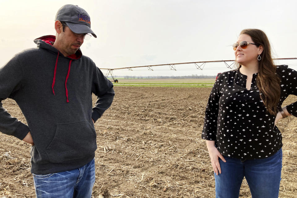 Farmer Lance Unger, left, and crop production specialist Kacee Bohle of Indigo Agriculture discuss techniques such as strip tillage and planting cover crops to improve soil health and yields while storing more carbon in the ground, in Carlisle, Indiana on April 6, 2021. The Biden administration is encouraging government and private initiatives that encourage such practices on farms as one strategy for fighting climate change while boosting the rural economy. (AP Photo/John Flesher)