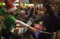 """An employee points to the touch pad for a customer to check out at a Toys""""R""""Us store during their Black Friday Sale in New York November 28, 2013. REUTERS/Carlo Allegri"""