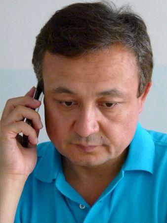 FILE PHOTO: Dolkun Isa, executive chairman of the World Uyghur Congress, speaks on his phone at the organization's Munich office