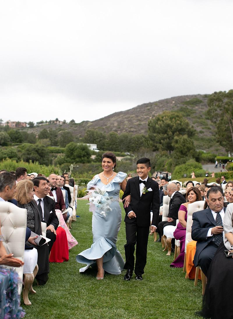 My stunning mother in a custom Nina Tiari gown, escorted down the aisle by my oldest nephew and her grandson, Kaveh Bakhtiari.